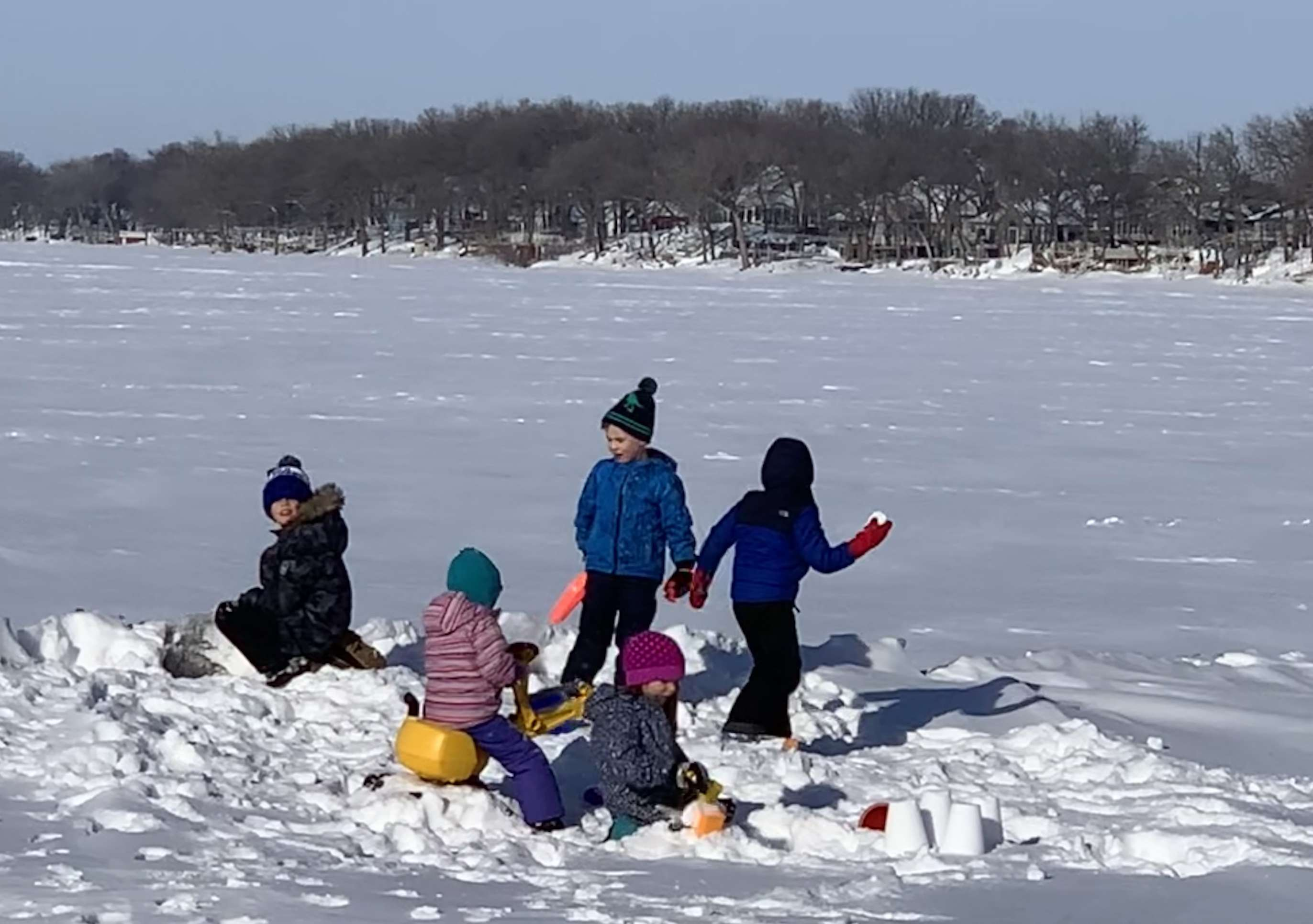 Five kids playing in the snow at Orleans Beach on Big Spirit Lake.
